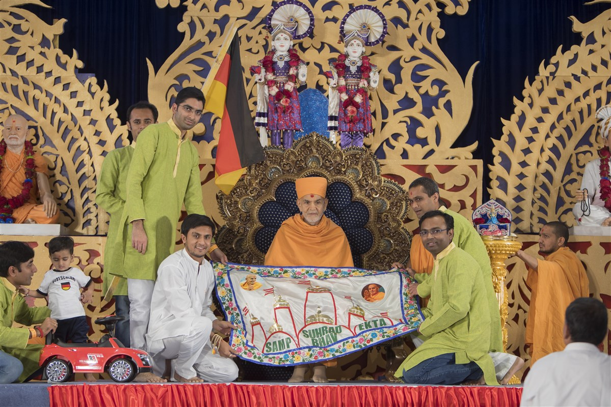 Devotees from Germany and Poland honour Swamishri with a decorative shawl