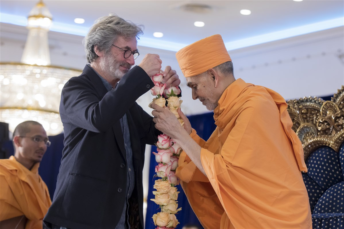 World-renowned multimedia show designer and producer, and consultant for two BAPS projects, Yves Pépin greets Swamishri with a flower garland