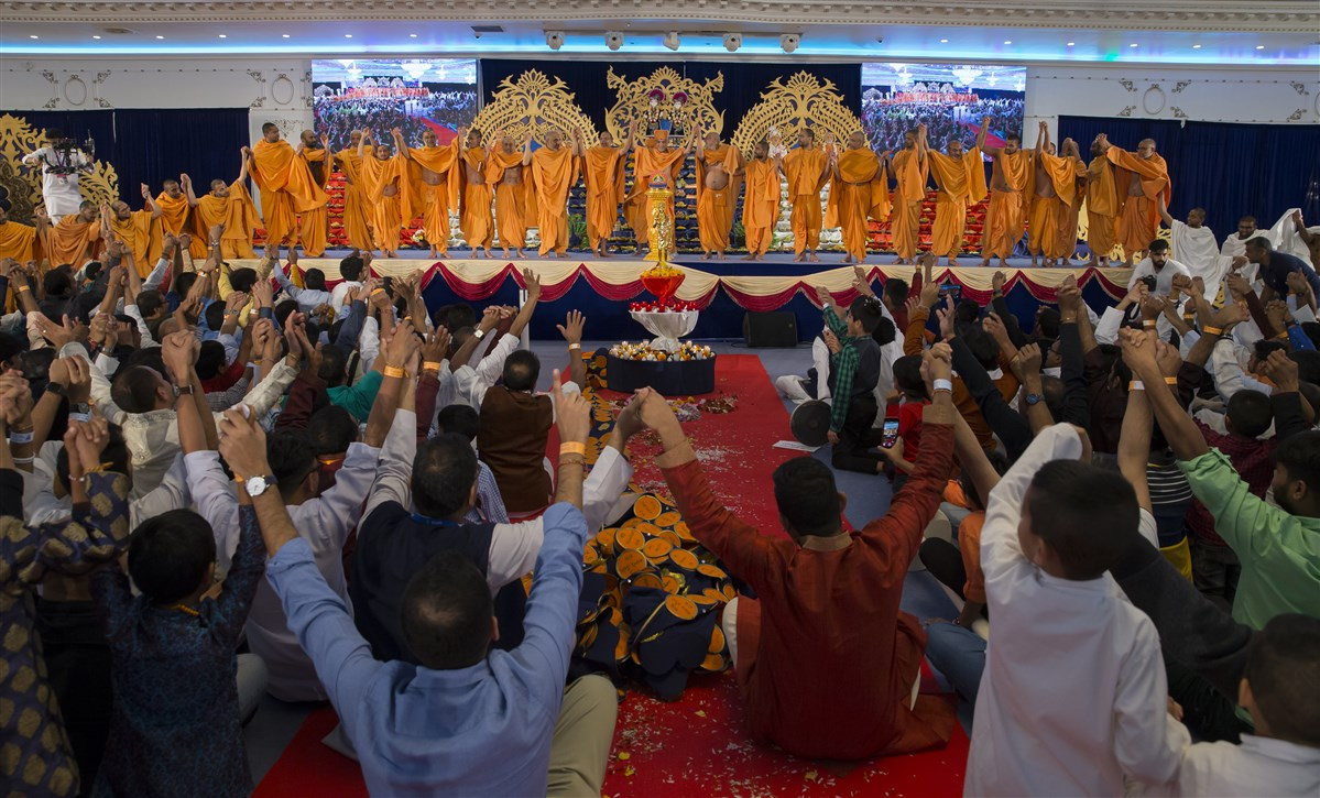 Swamishri links hands with swamis and devotees...