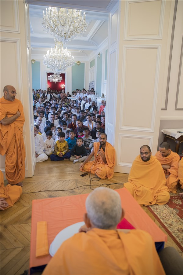 Paramsevadas Swami introduces to Swamishri volunteers from various European countries