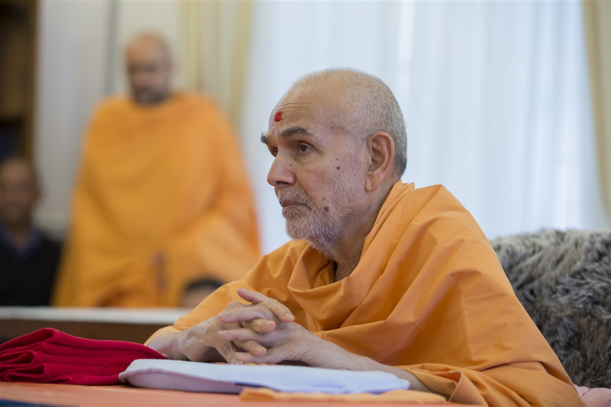 Swamishri listens attentively to the report