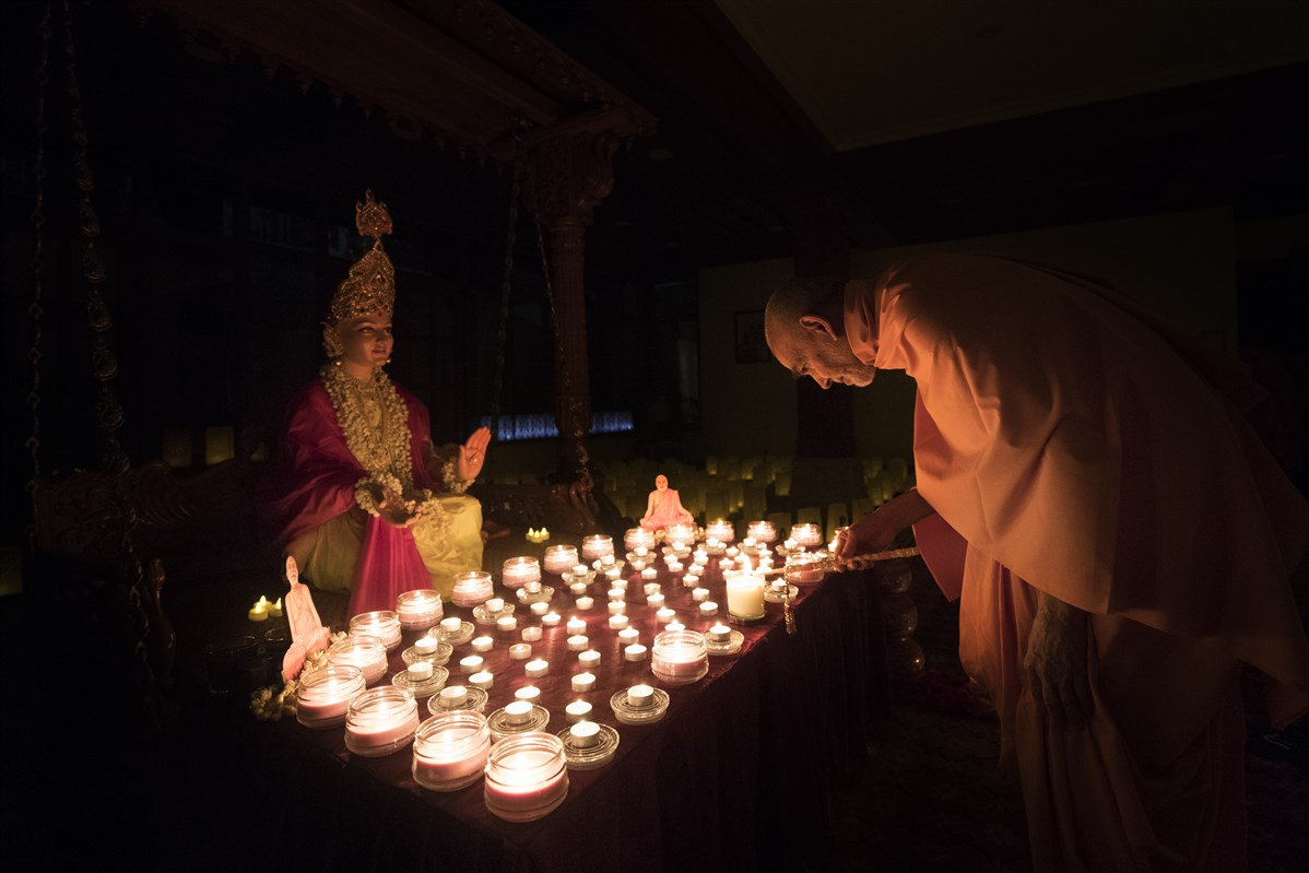 ... by lighting a divo before the murti of Bhagwan Swaminarayan