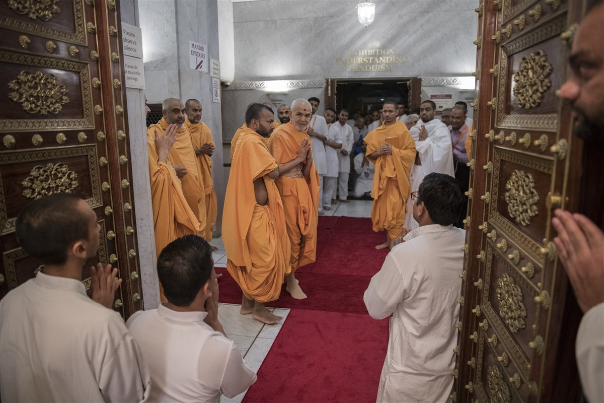 Swamishri looks back with folded hands into the Abhishek Mandap to Shri Nilkanth Varni as he proceeds towards the assembly hall
