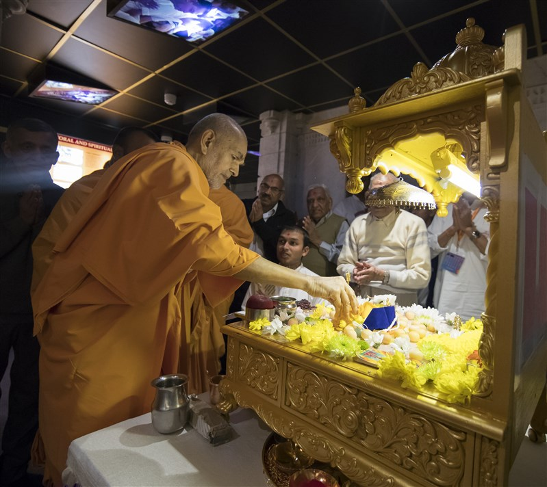 Swamishri honours the mahapuja with flower petals