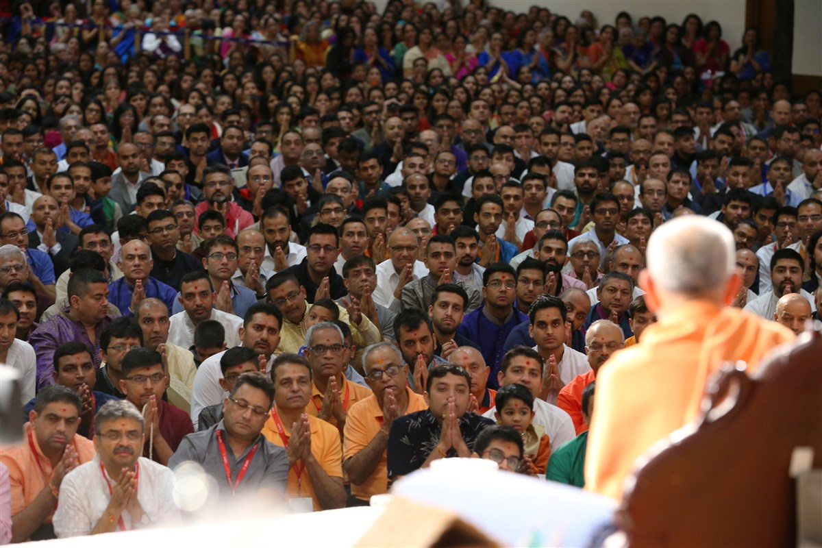 Devotees greet Swamishri with folded hands