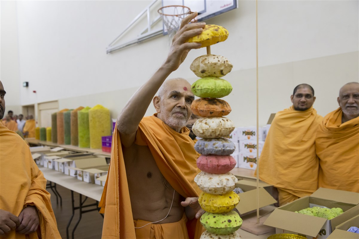 Swamishri completes a decorative offering for the annakut