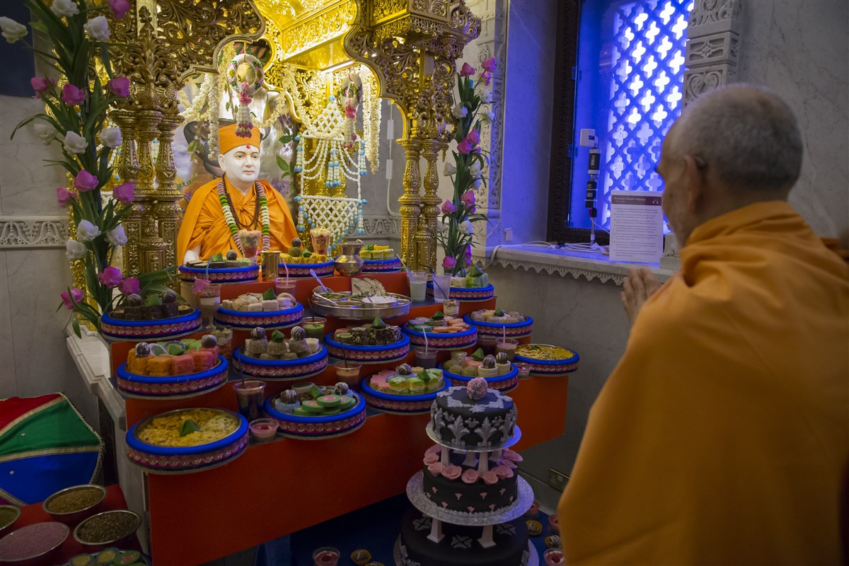 Swamishri engrossed in the annakut offering to Pramukh Swami Maharaj