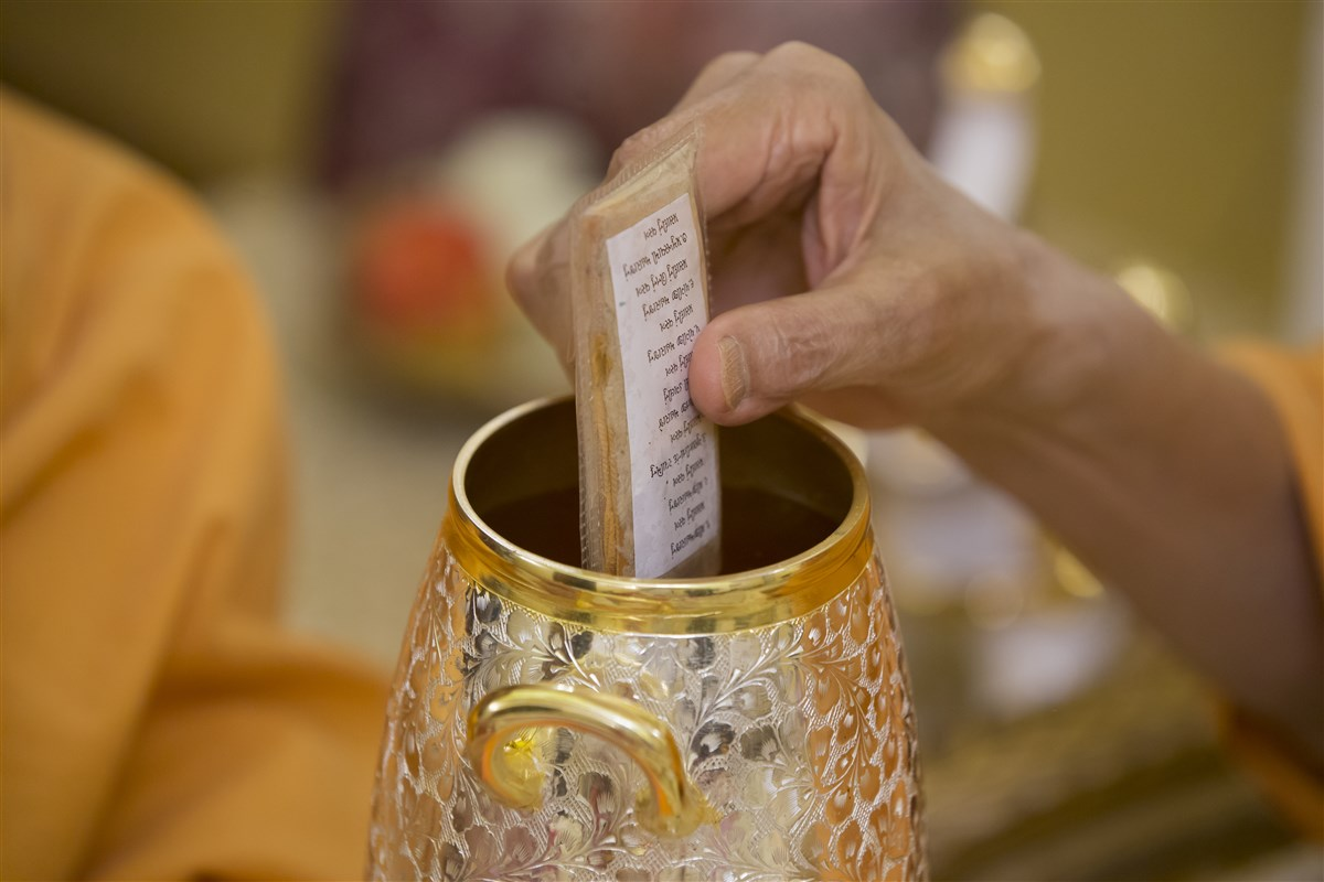 Swamishri sanctifies water with the holy relics of Bhagwan Swaminarayan and the Guru Parampara