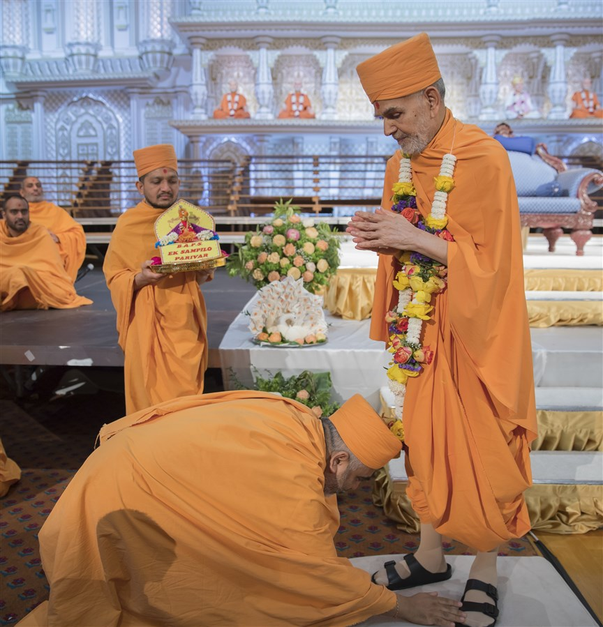 Yogvivekdas Swami bows before Swamishri after honouring him with a garland