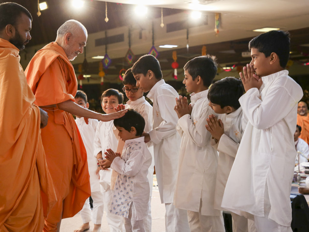 Swamishri blesses children who presented in his morning puja