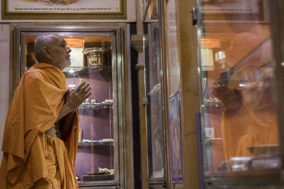Swamishri engrossed in darshan of holy relics of Shri Guru Parampara
