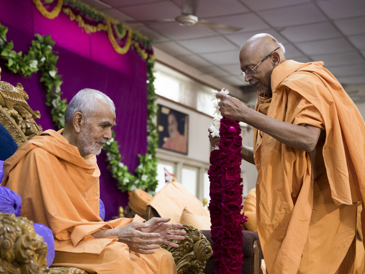 Pujya Tyagvallabh Swami welcomes Swamishri with a garland