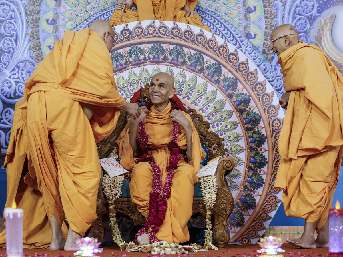 Pujya Ishwarcharan Swami and Pujya Tyagvallabh Swami honor Swamishri with a garland