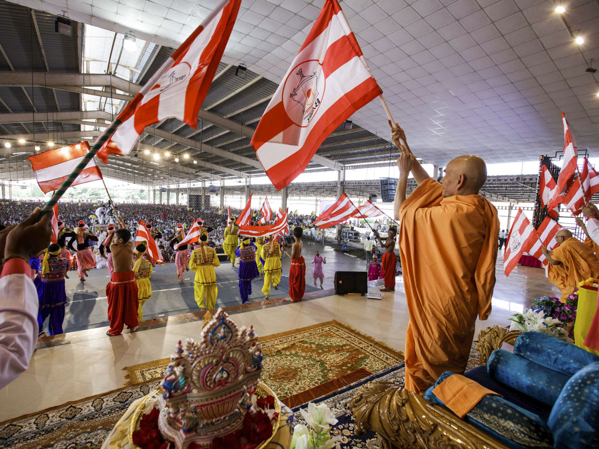 Swamishri and children wave BAPS flags