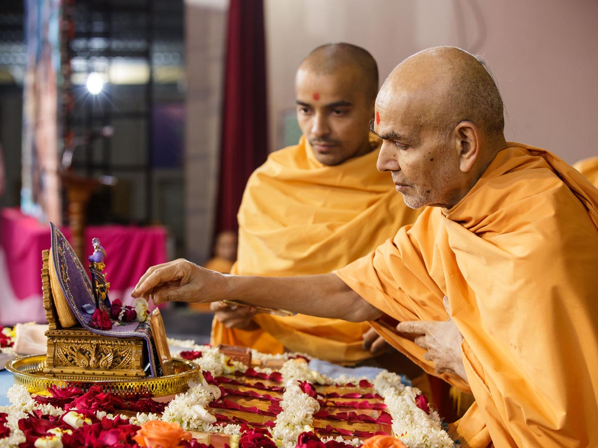 Swamishri reverentially touches charanarvind of Shri Harikrishna Maharaj