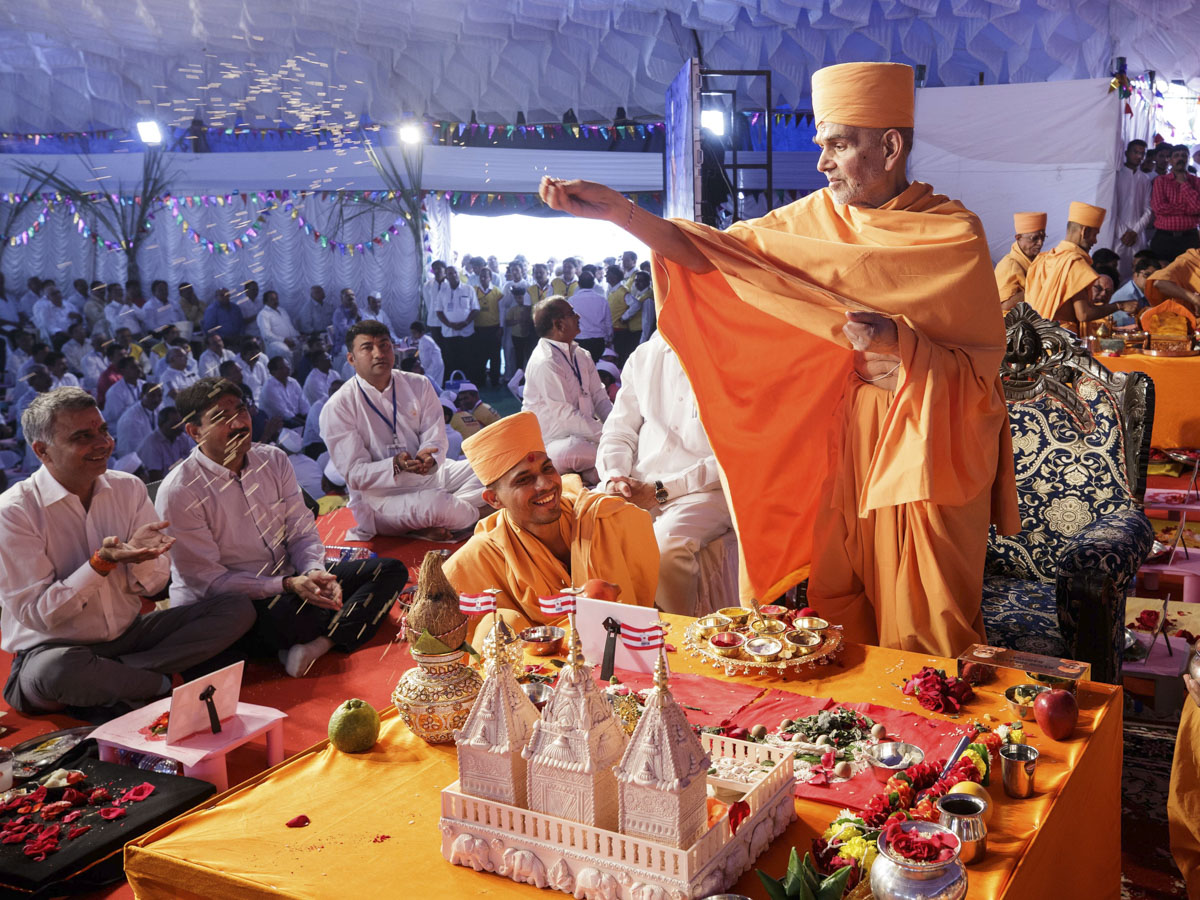 Swamishri blesses devotees by showering rice grains