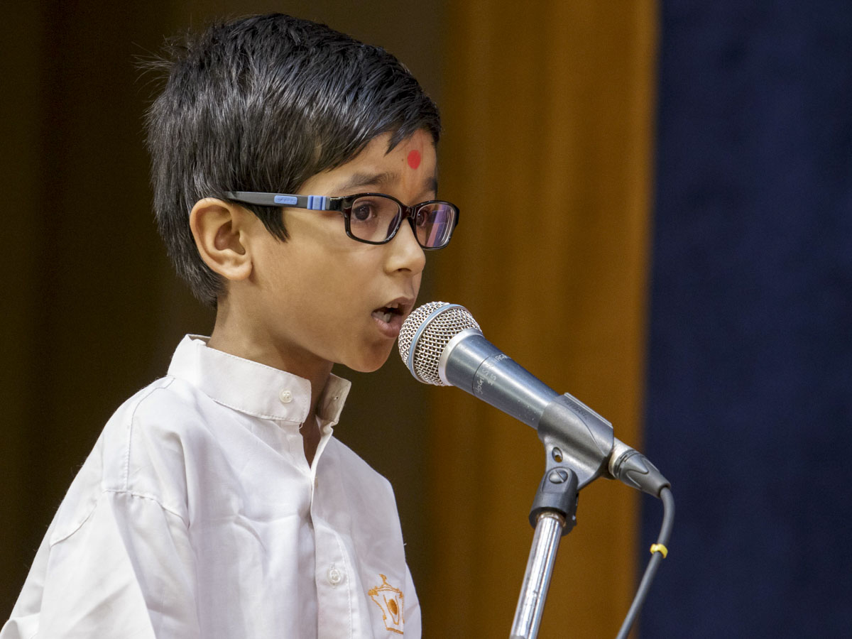 A child presents in Swamishri's puja