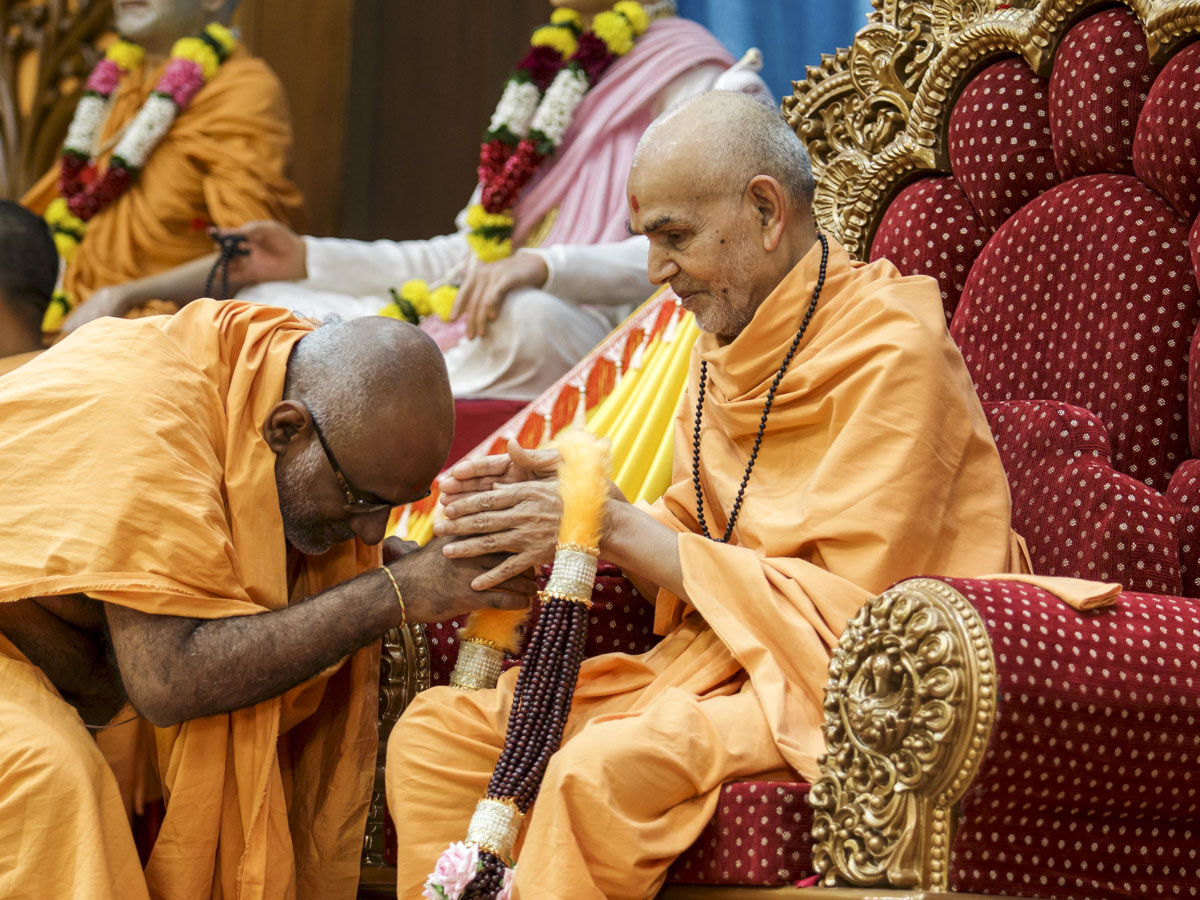 Abhayswarup Swami honors Swamishri with a garland