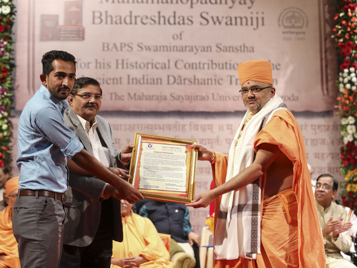 Dr. K. R. Desai and a representative of Uka Tarsadia University honor Bhadresh Swami