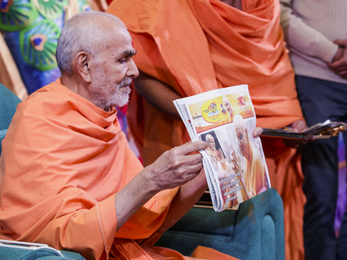 Swamishri sanctifies a special supplement in honor of Pramukh Swami Maharaj's birthday published by 'Divya Bhaskar'