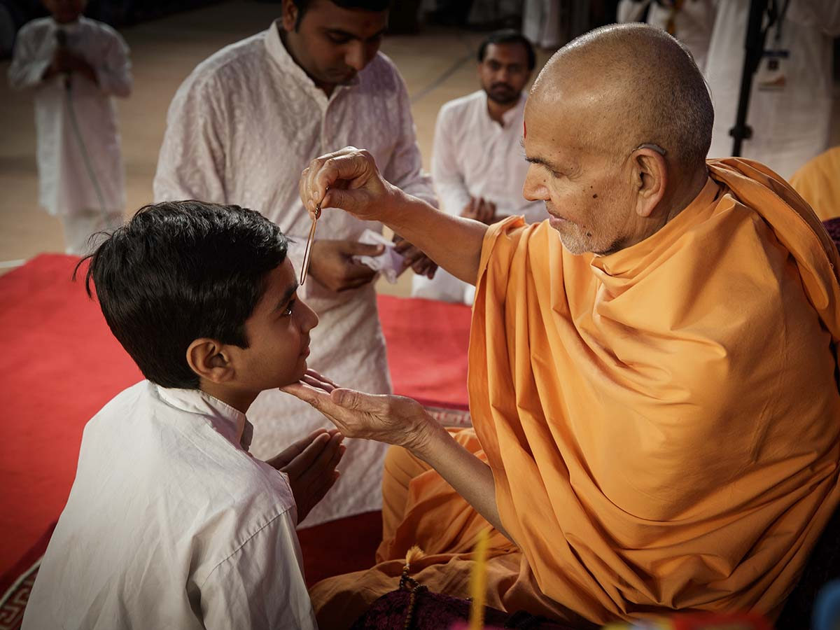 Swamishri applies tilak to a child