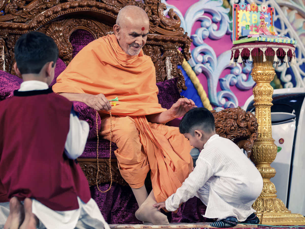 A child bows at the feet of Swamishri
