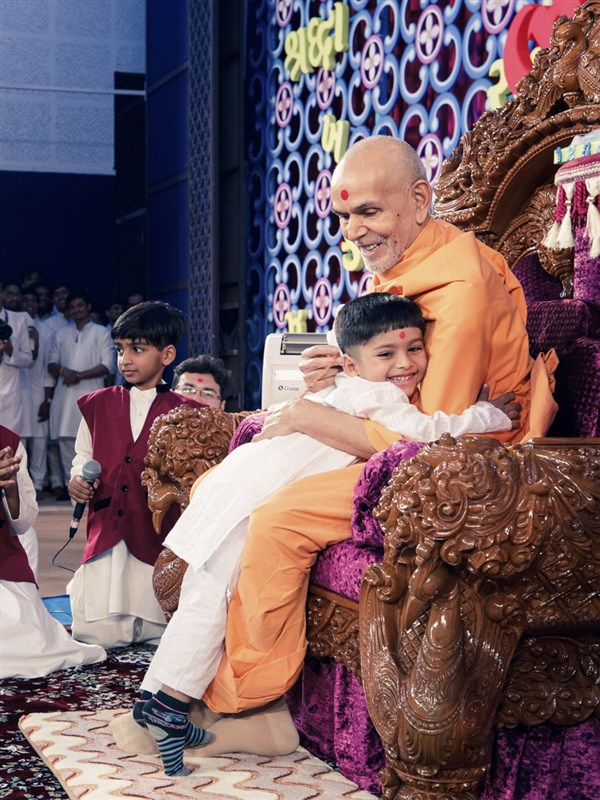 A child embraces Swamishri