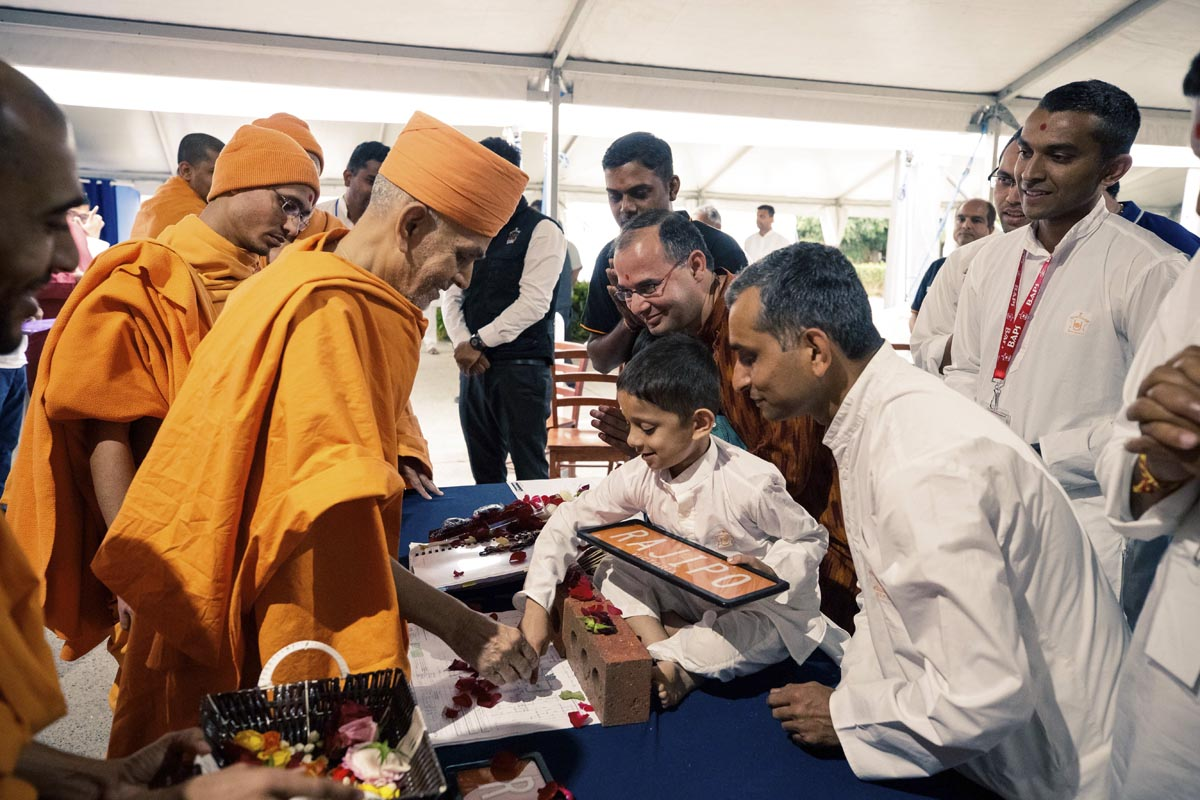 Swamishri sanctifies a plan and bricks for a new home