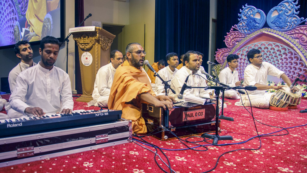 A sadhu sings a kirtan in Swamishri's morning puja
