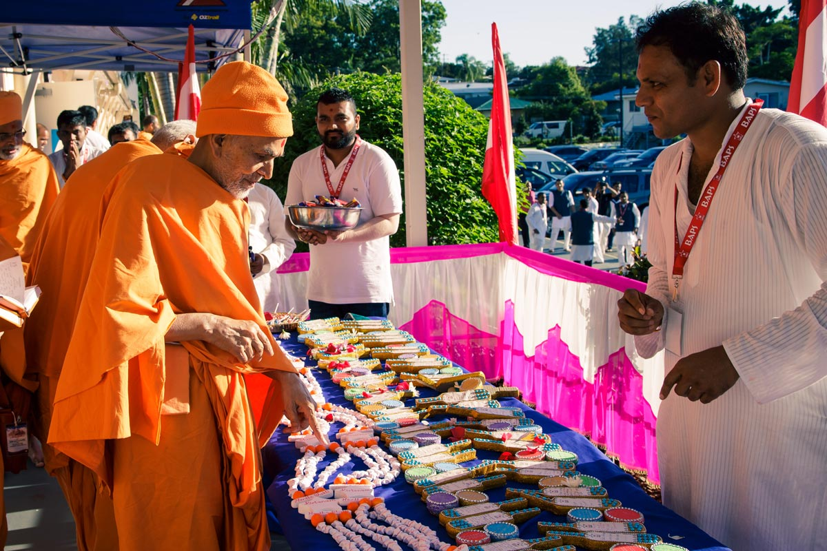 Swamishri sanctifies a garland and cricket bats and balls on which children have written Swamini Vatos and other messages