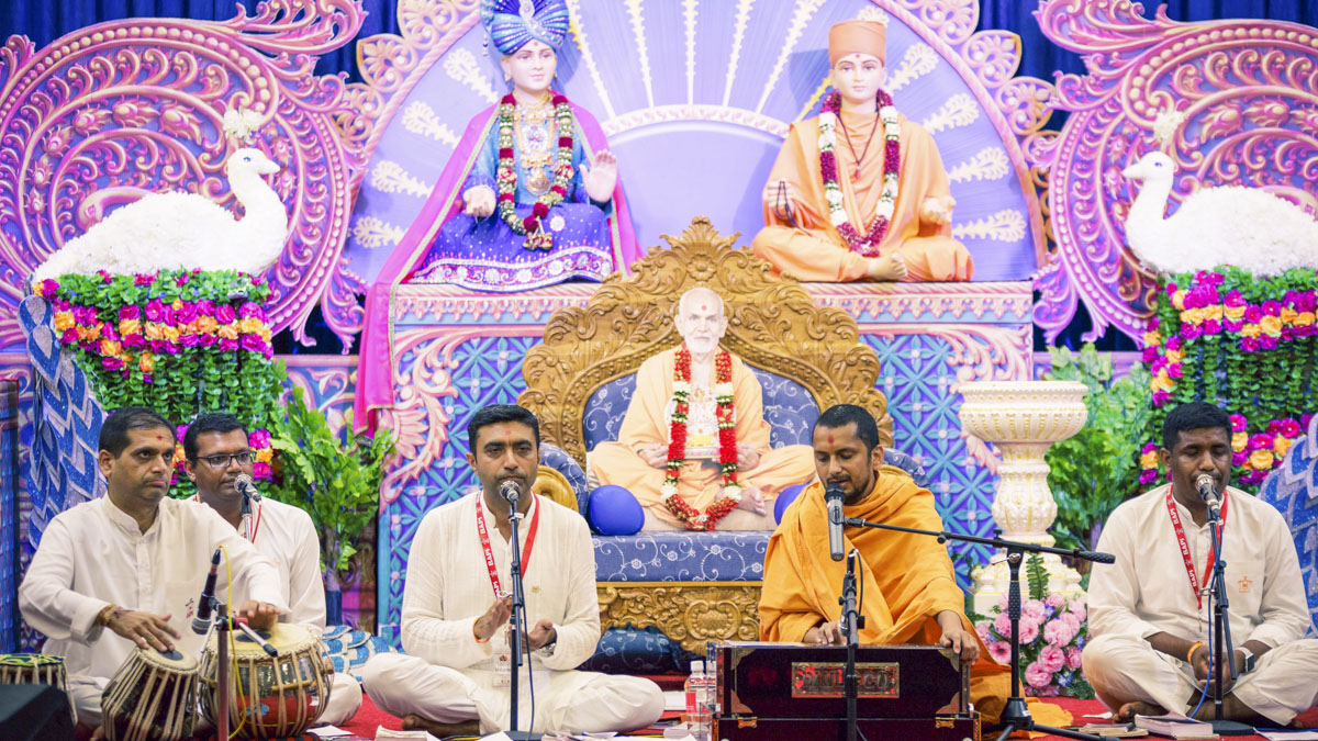 A sadhu and youths sing kirtans during the evening assembly