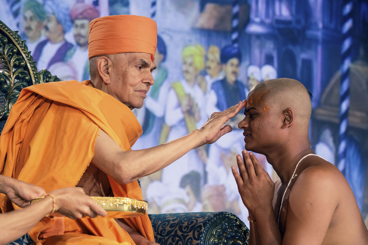 Swamishri applies chandlo to newly initiated parshad