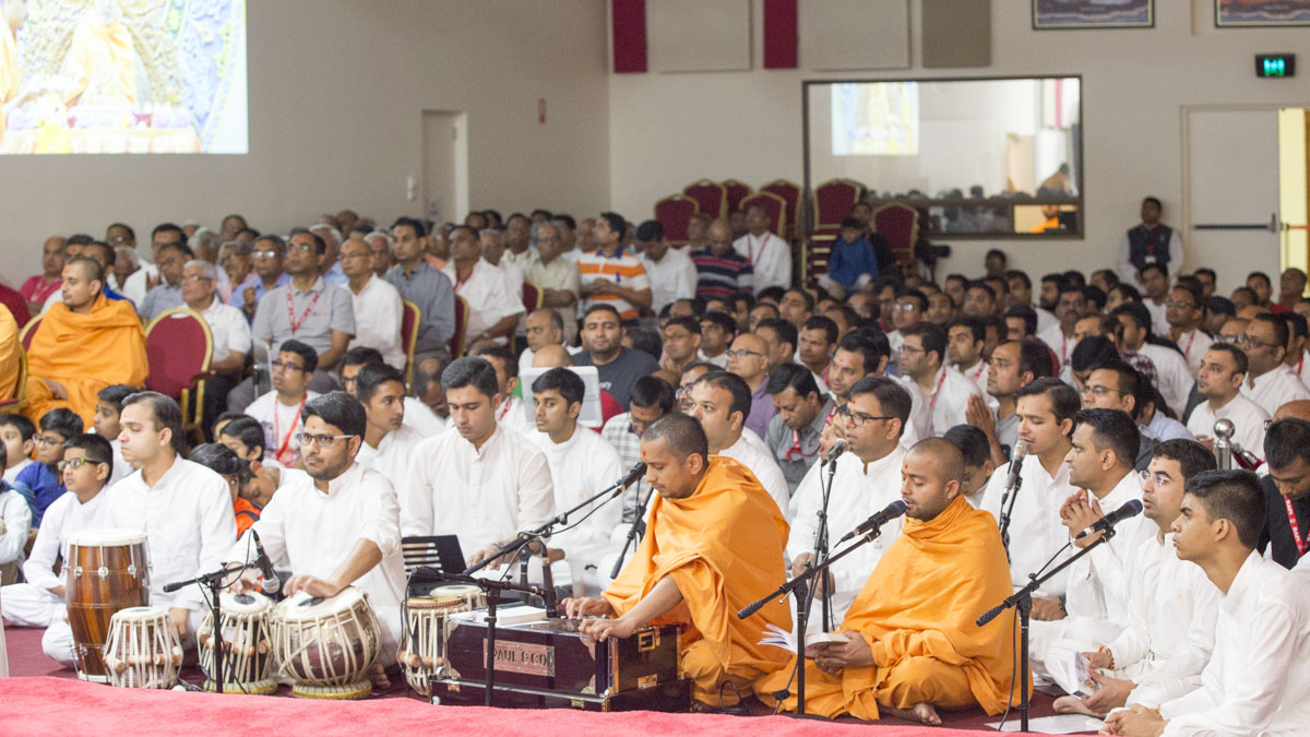 Sadhus and youths sing kirtans during Swamishri's puja