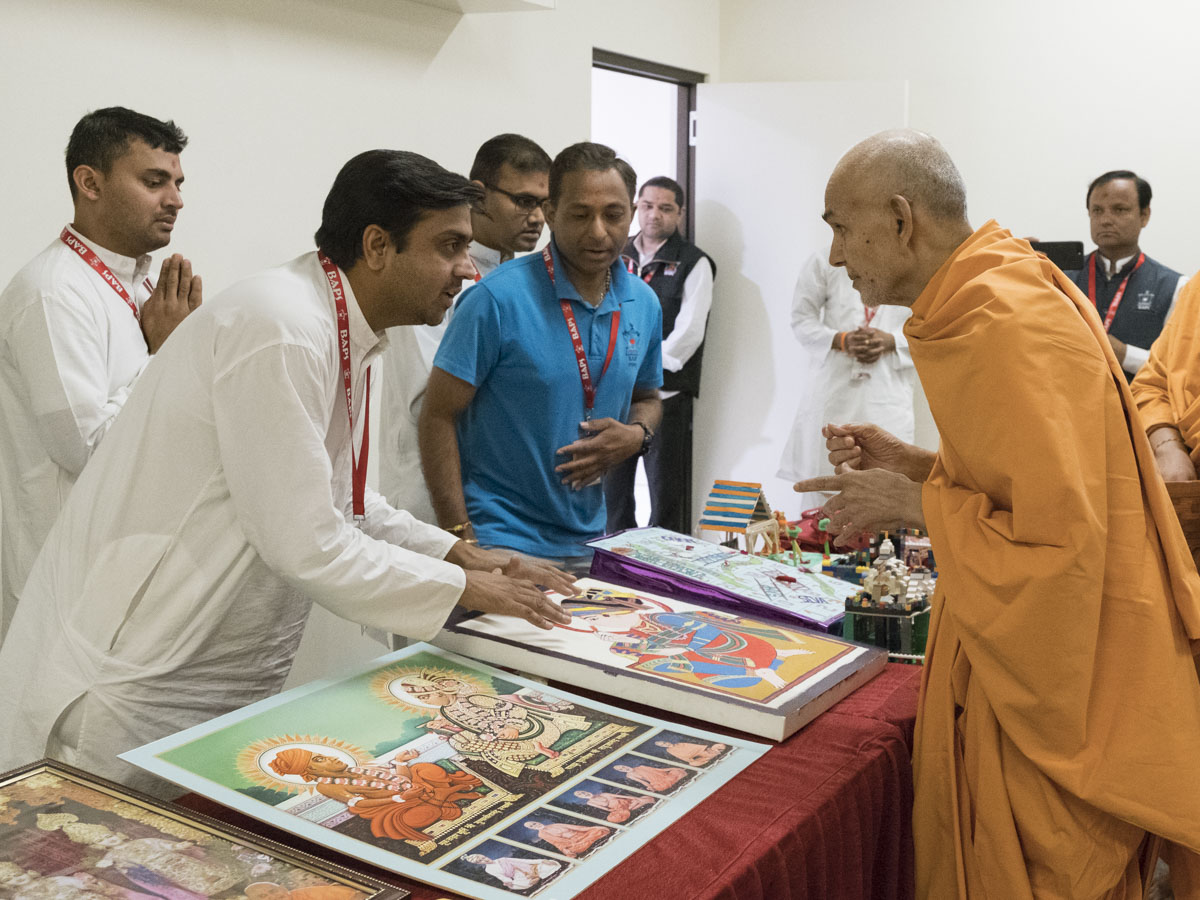 Swamishri sanctifies a painting prepared by a devotee
