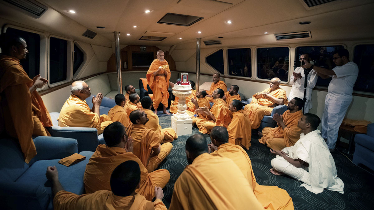 Swamishri performs the evening arti in the boat after the asthipushpa visarjan rituals