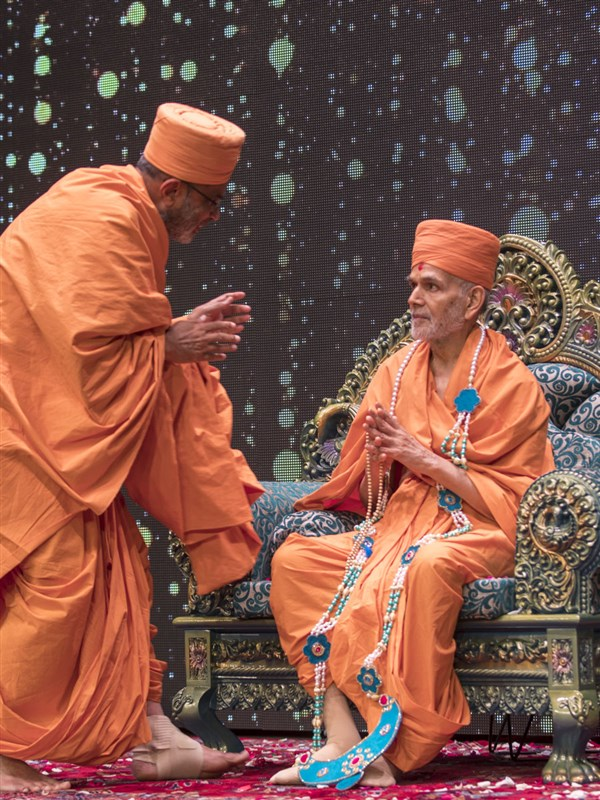 Gnaneshwar Swami honors Swamishri with a garland