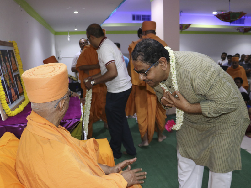 Devotees welcome Pujya Doctor Swami with a garland