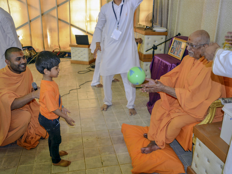 A child interacts with Pujya Doctor Swami