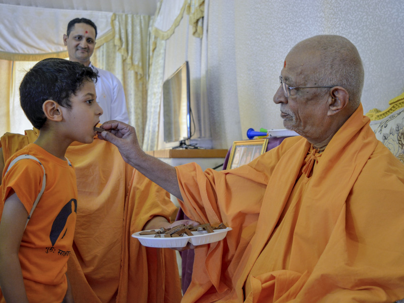 Pujya Doctor Swami gives prasad to a child