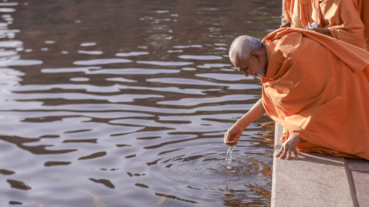 Swamishri applies holy water of Narayan Kund on his head