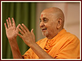 After his puja, Swamishri responds to the kirtan with joy