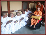 Swamishri sanctifies the eating bowls of newly initiated sadhus and parshads by showering flower petals