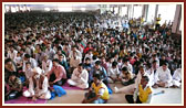 Devotees in the assembly hall engaged in Swamishri's puja darshan