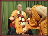 Senior sadhus welcome Swamishri with garlands