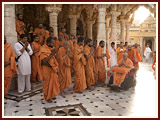 Sadhus engaged in Swamishri's darshan in the mandir pradakshina