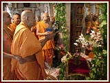Swamishri sprays color on Thakorji on symbolic celebration of Pushpadolotsav