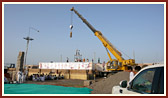 First pillar lifted by crane and being placed on mandir plinth