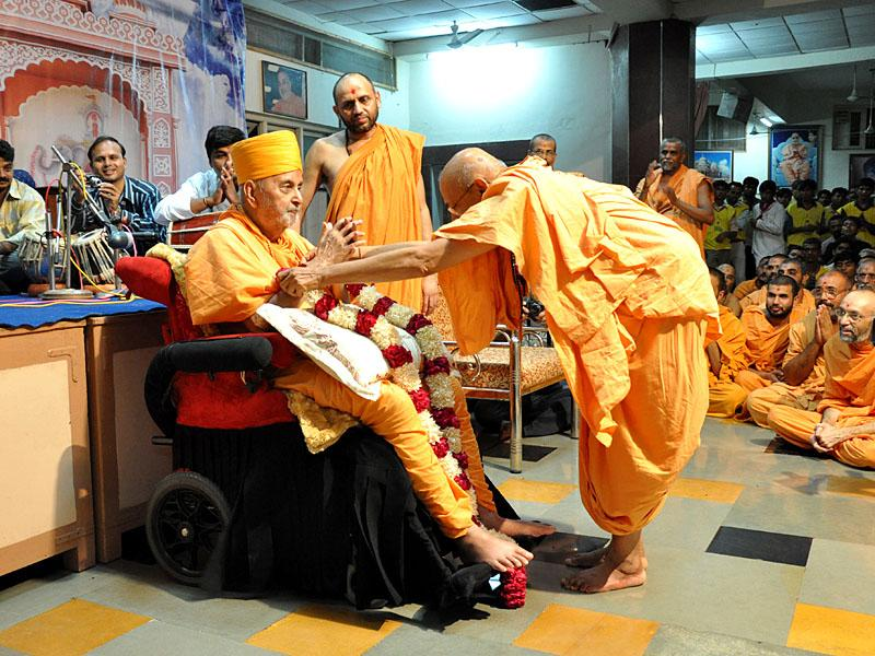 Pujya Tyagvallabh Swamishri welcomes Swamishri with a garland