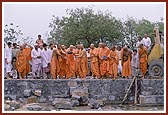 Swamishri places a stone in the foundation pit and offers his service