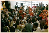 Swamishri seated amongst devotees at Terminal 3 listening to Viveksagar Swami